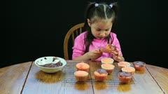 Little girl eating yummy homemade cupcakes at kitchen table Stock Footage