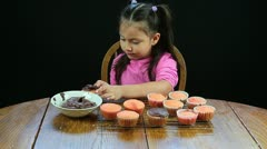 Young girl frosting chocolate cupcakes Stock Footage