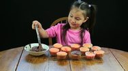 Young girl spreading chocolate frosting on cupcakes Stock Footage