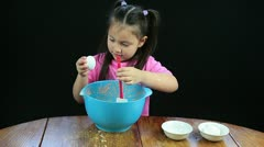 Hd of child cracking an egg into bowl filled with cake batter Stock Footage