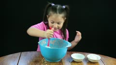 Hd of five year old girl mixing batter with a spatula in a blue bowl Stock Footage