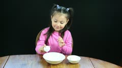 Five year old girl cracking eggs Stock Footage