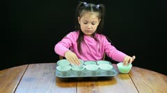 Child filling muffin tins Stock Footage