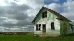 Abandoned farm house, green and white, wide open prairie Stock Footage