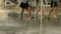 Girls wearing slippers and walking through fountain of park Stock Footage