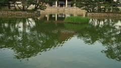 Tilt-up shot of Gyeonghoeru pavilion surrounded by pond in Seoul Stock Footage