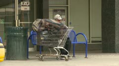 homeless man sitting on a bench with his shopping cart - stock footage
