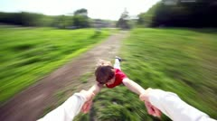 Hand holds little boy which flies above grass Stock Footage