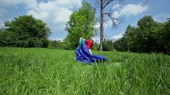 Little boy pitches tent on grass glade under blue sky - stock footage