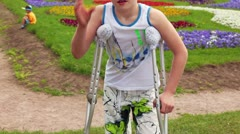 Boy stand with crutches, his injured leg has broken finger Stock Footage