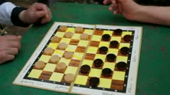 People play draughts on table, only hands are visible Stock Footage