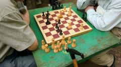 Two men sit and think under chessboard, closeup view of table Stock Footage
