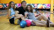 Boy and girls sit and simulate rowing on floor in bowling club Stock Footage