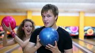 Two girls stand behind boy and they dance with bowling balls Stock Footage