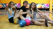 Two girls with one guy sit on floor and dance at bowling club Stock Footage