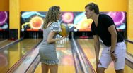 Girl throws bowling ball to beat skittles, boy jumps very happy Stock Footage