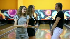 Two girls with one guy dance together at bowling club Stock Footage