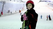 Girl stands with ski at background of snow slope and ropeway Stock Footage