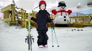 Little girl in warm clothes and helmet stands with skis Stock Footage