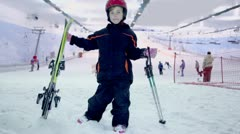 Girl stands with ski and poles at background of snow slope Stock Footage
