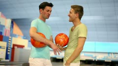Two friends stand in bowling club with balls and talk Stock Footage