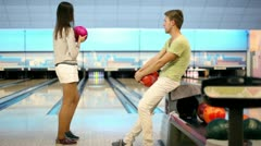 Girl throws bowling ball, boy raises hands satisfied with result Stock Footage