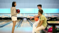 Two boys watch how girl makes throw in bowling game Stock Footage