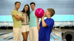 Students team watch on little boy throws bowling ball Stock Footage