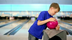 Boy takes ball and throws it to beat skittles on bowling lane Stock Footage
