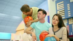 Three students boys with girl sit and talk in bowling club Stock Footage