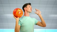 Young man hold bowling ball and drink water from plastic bottle Stock Footage