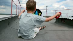 boy sit on roof and hold shroud lines, parachute inflated by air - stock footage