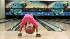Little girl in pink clothes throws bowling ball and runs away Stock Footage