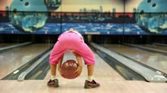 Little girl throws bowling ball, then jumps and walks away - stock footage