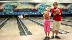Kids stand in bowling club, then girl walks away, boy make throw Stock Footage