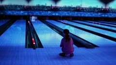 Girl watch on ball trundles by bowling lane and beats skittles Stock Footage