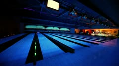 Ball rolls and beats skittles on bowling lane with illumination - stock footage