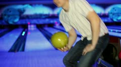 Young man throws bowling ball to beat skittles in dark club - stock footage