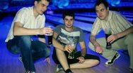 Three friends sit and drink bear in dark bowling club Stock Footage