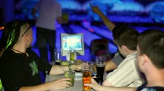 Young man plays bowling and his friends drink beer in dark club Stock Footage