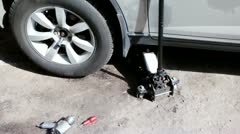 Lifting jack under car, few tools lie near, shown in motion Stock Footage