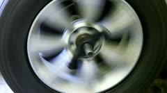 Car wheels spins, man stops it and fixates Stock Footage