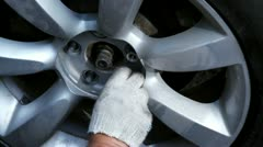 Hands in glove screw up nuts on car wheel, closeup view Stock Footage