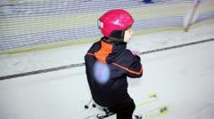 Little girl helmet holds rope and slide on ski - stock footage