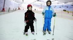 Two kids stand on ski and raises poles at background of ropeway Stock Footage