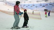 Mother with daughter stand on ski and talk Stock Footage
