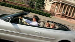 Belt up family ride in cabriolet near huge architectural complex Stock Footage