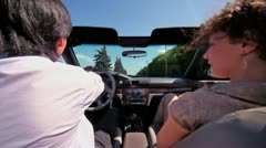 Couple sit in cabriolet and ride by road at sunny summer day Stock Footage
