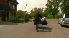 Homeless man and cart, wide shot Stock Footage