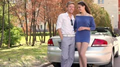 Young couple stand near cabriolet with rear light blink Stock Footage